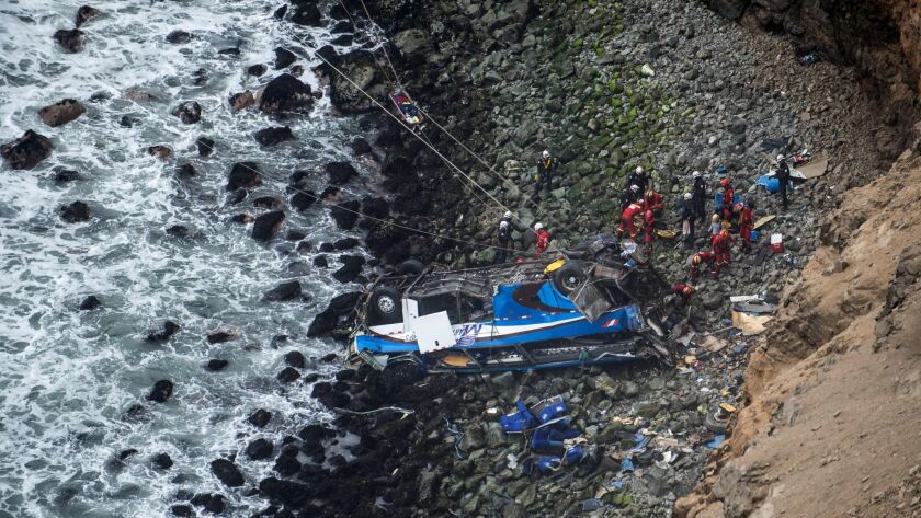 Rescuers, police and firefighters work at the scene after a bus collided with a truck and plunged over a cliff on a coastal highway near the Peruvian city of Pasamayo.