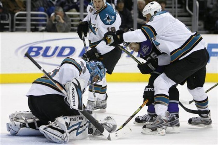 San Jose Sharks goaltender Brian Boucher, left, covers the puck as defenseman Rob Blake, right, prevents Los Angeles Kings' Michal Handzus, of the Czech Republic, from reaching a rebound during the second period of an NHL hockey game Monday, Dec. 15, 2008, in Los Angeles. (AP Photo/Danny Moloshok)