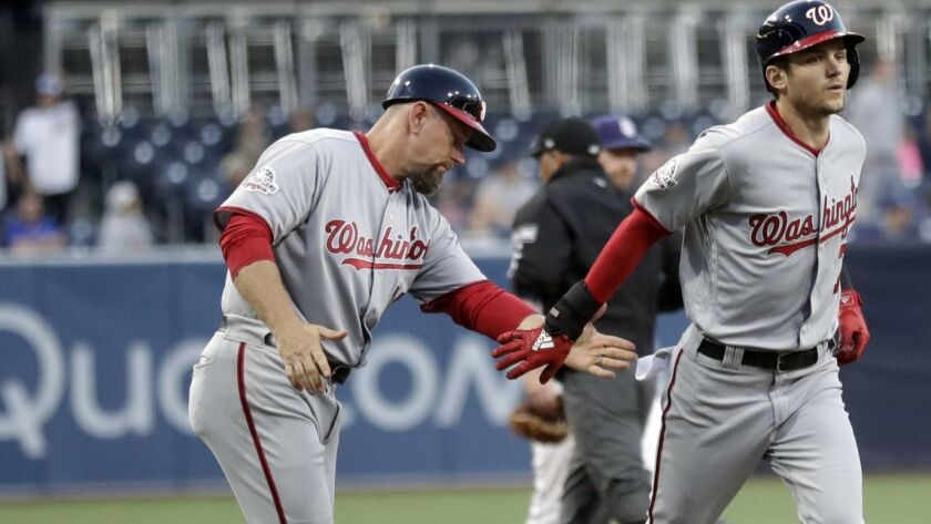 Washington Nationals' Trea Turner, right, is greeted by third base coach Bob Henley after hitting a