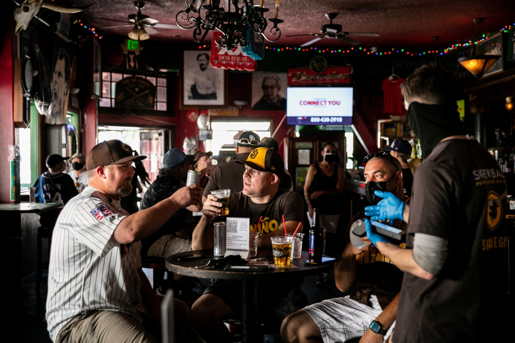 Robbie Deburn and Matt Lowery cheers their drinks at Tivoli Bar before the start of the Opening Day game.