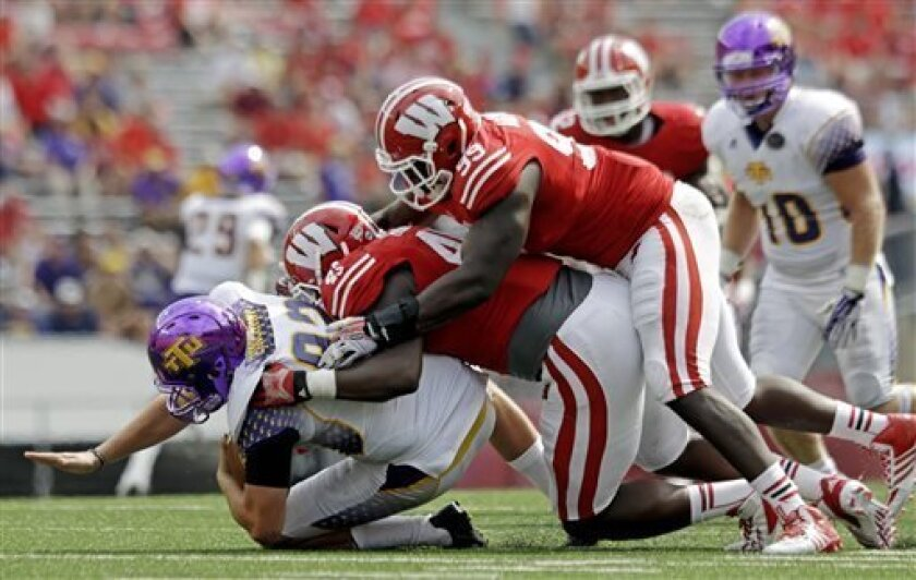 Wisconsin's Warren Herring (45) and James Adeyanju (99) tackle Tennessee Tech punter Chad Zinchini during the second half of an NCAA college football game Saturday, Sept. 7, 2013, in Madison, Wis. Wisconsin won 48-0. (AP Photo/Morry Gash)