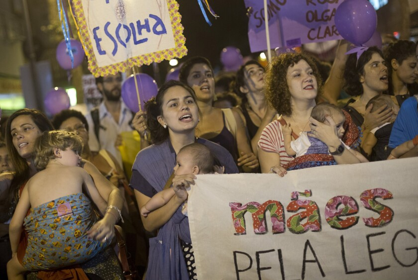Mothers carry their children as they protest demanding the legalization of abortion during a demonstration to mark International Women's Day, in Rio de Janeiro, Brazil, on March 8, 2016.