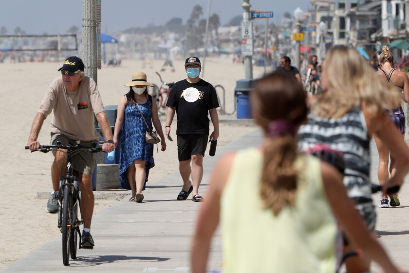 A man and woman wear face masks as they walk along the bike path toward the Newport Beach Pier on Sept. 4.