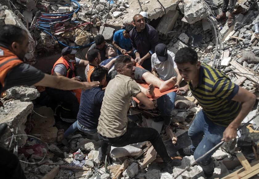 Palestinos sacan a un sobreviviente entre los escombros de un edificio residencial destruido