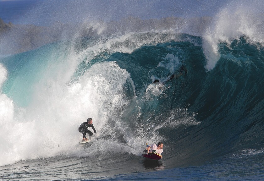 A surfer and a bodyboarder ride a big wave at the Wedge in Newport Beach last summer. Similar waves are expected this weekend.