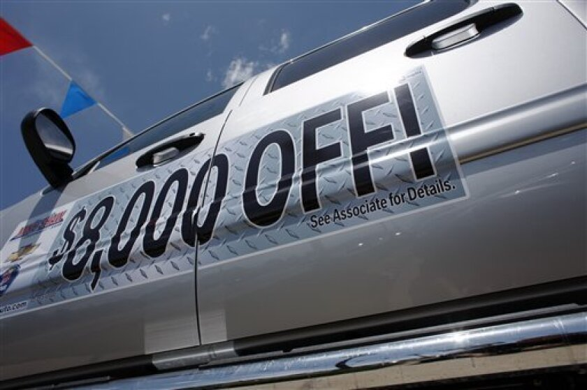 In this photograph taken May 9, 2010, a discount available is posted on the side of a 2010 Chevrolet Silverado pickup truck at a Chevrolet dealership in east Denver. General Motors Co. said Wednesday, June 2, 2010, its May sales rose 17 percent on strong new product sales and a big government fleet contract. (AP Photo/David Zalubowski)