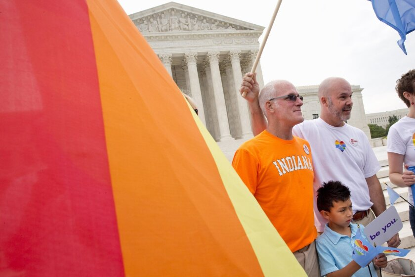 Rodney Moubray-Carrico and Scott Moubray-Carrico, who are among the Indiana plaintiff's, stand with their son Lucas, 7, outside of the Supreme Court in Washington on Friday. The Court narrowly affirmed, in occasionally eloquent terms, their right to be married.