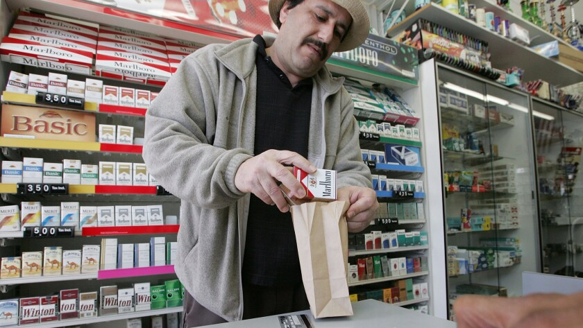 Shop owner Izzat Asfour sells a pack of cigarettes to a customer in San Francisco.