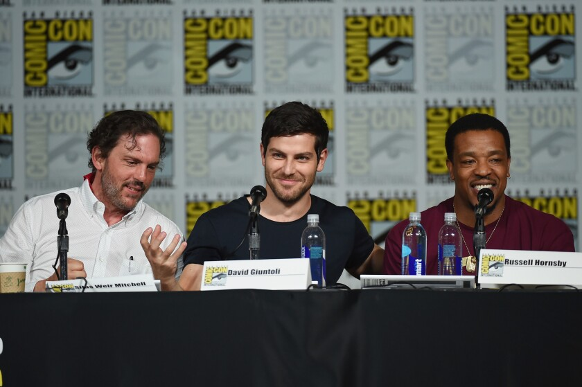 """Actors Silas Weir Mitchell, left, David Giuntoli and Russell Hornsby speak onstage at the """"Grimm"""" season 5 panel during Comic-Con International 2015."""