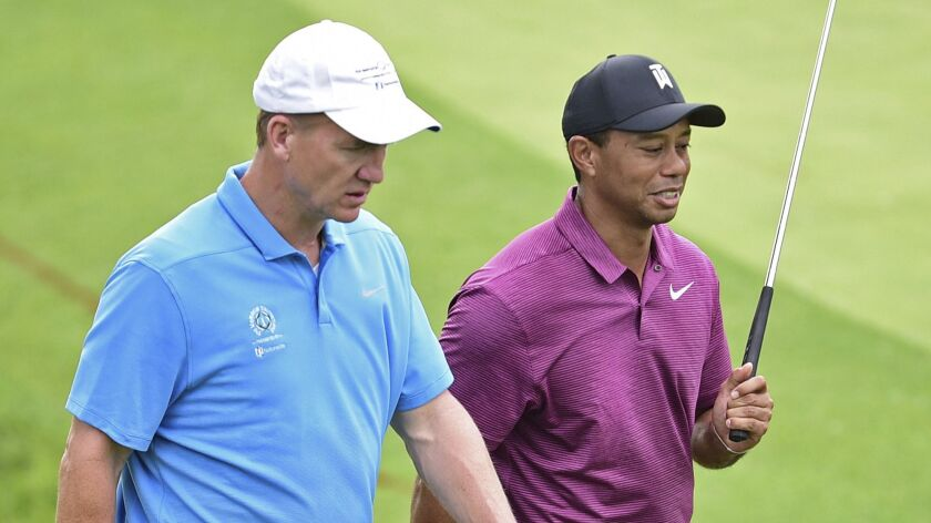 Peyton Manning, left, and Tiger Woods walk to the green on the eleventh hole during the pro-am for t