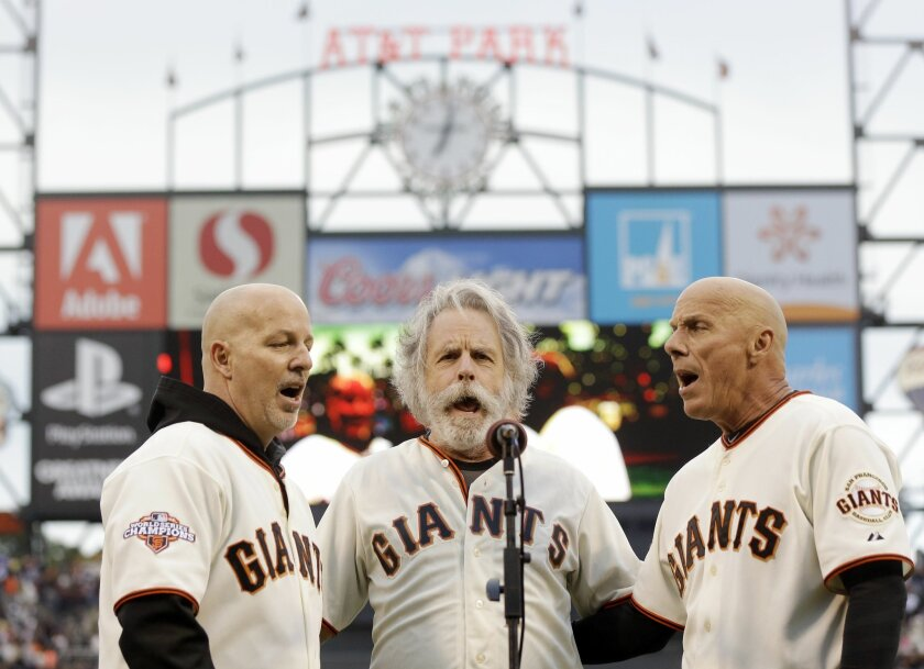 File - In this Aug. 5, 2013 file photo, San Francisco Giants third base coach Tim Flannery, right, and his brother Tom, left, sing the national anthem with Bob Weir of the Grateful Dead before a baseball game against the Milwaukee Brewers in San Francisco. Flannery, the San Francisco Giants' third-base coach and musician, presented the family of Bryan Stow with $96,000 during the weekend to help with his care as he continues to deal with traumatic injuries and brain damage from being severely beaten outside Dodger Stadium on opening day 2011. (AP Photo/Marcio Jose Sanchez, file)