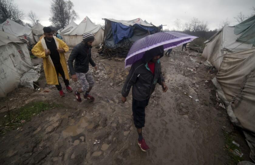 Migrants walk Nov. 16 in the Vucjak refugee camp outside Bihac, northwestern Bosnia.