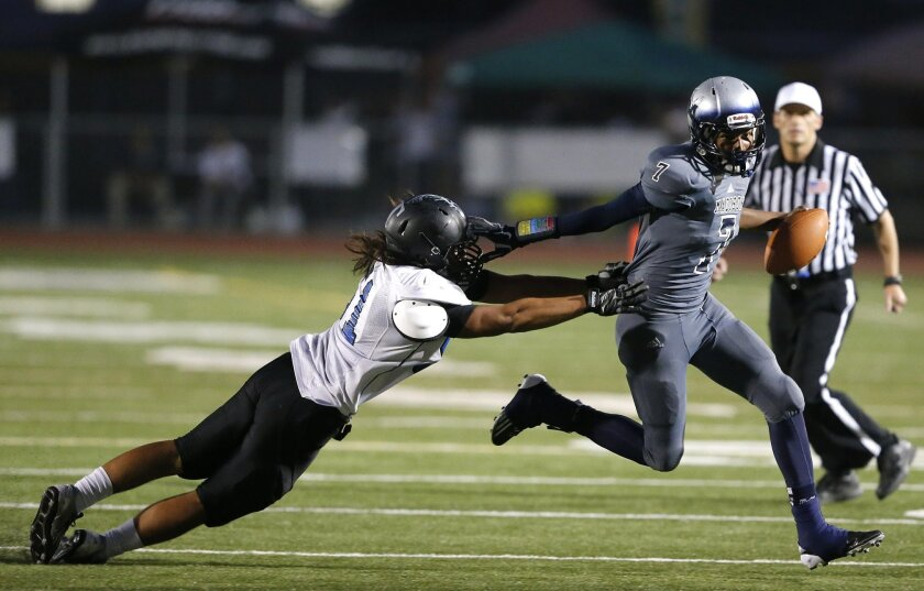 Madison's quarterback Kareem Coles stiff arms Eastlake's Mathieu Lao in the 2nd quarter as Madison High School hosted Eastlake High School in prep football Friday night.