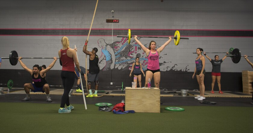 Allison Truscheit, left, observes her clients while they practice barbell lifts.