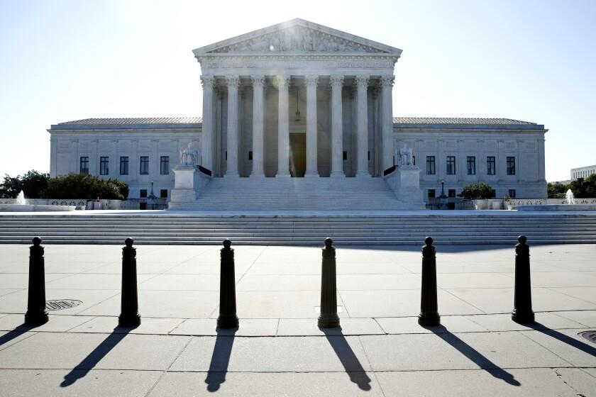 Fotografía del sol saliendo atrás de la Corte Suprema en el Capitolio,