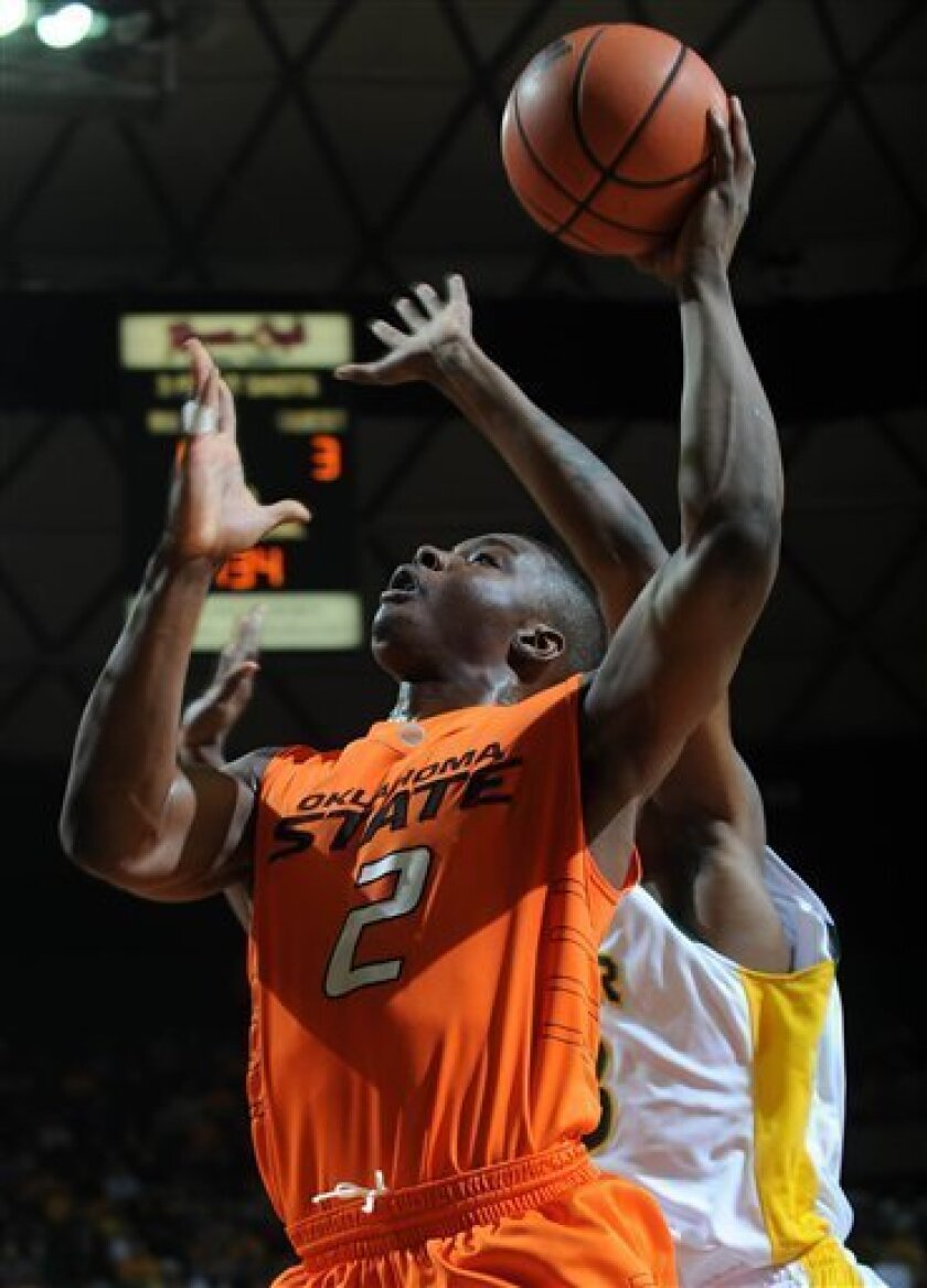 Oklahoma State guard Obi Muonelo (2) shoots past Baylor's forward Kevin Rogers, right, during the first half of an NCAA college basketball game Saturday Jan. 17, 2009, in Waco, Texas. (AP Photo/Rod Aydelotte)