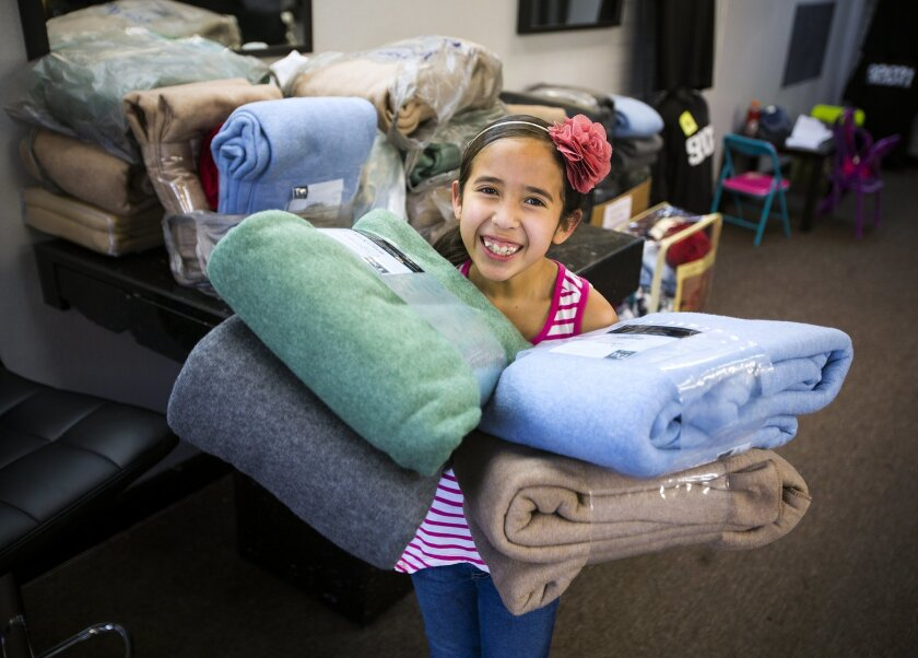 Eight-year-old Gabriela Betancourt holds some of the more than 40 blankets she's collected at her dad's business, Raymond's Barber Shop,  and will distribute them to homeless people in the downtown area of San Diego in the later part of February.