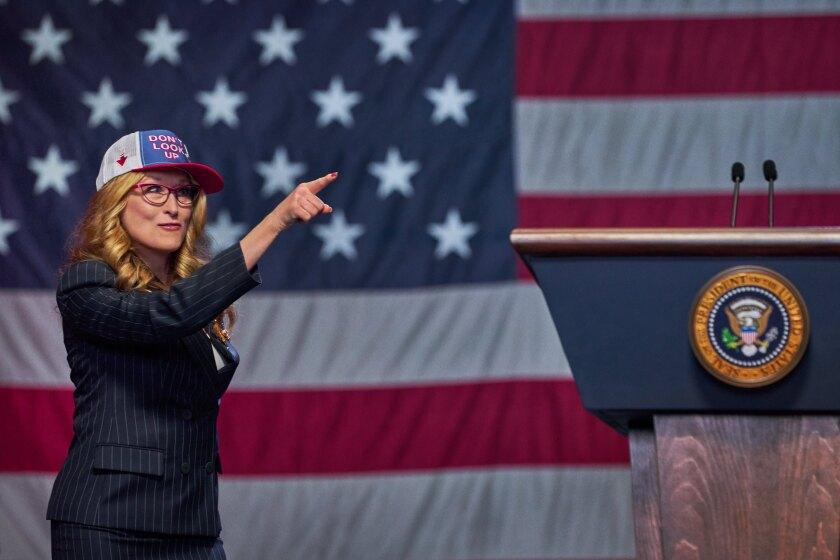 एक सूट और बेसबॉल टोपी में एक महिला एक विशाल अमेरिकी ध्वज के सामने इशारा करती है।