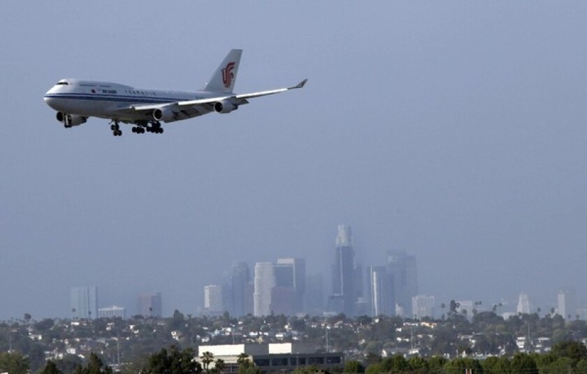 A plane approaches LAX for a landing with downtown Los Angeles in the background.