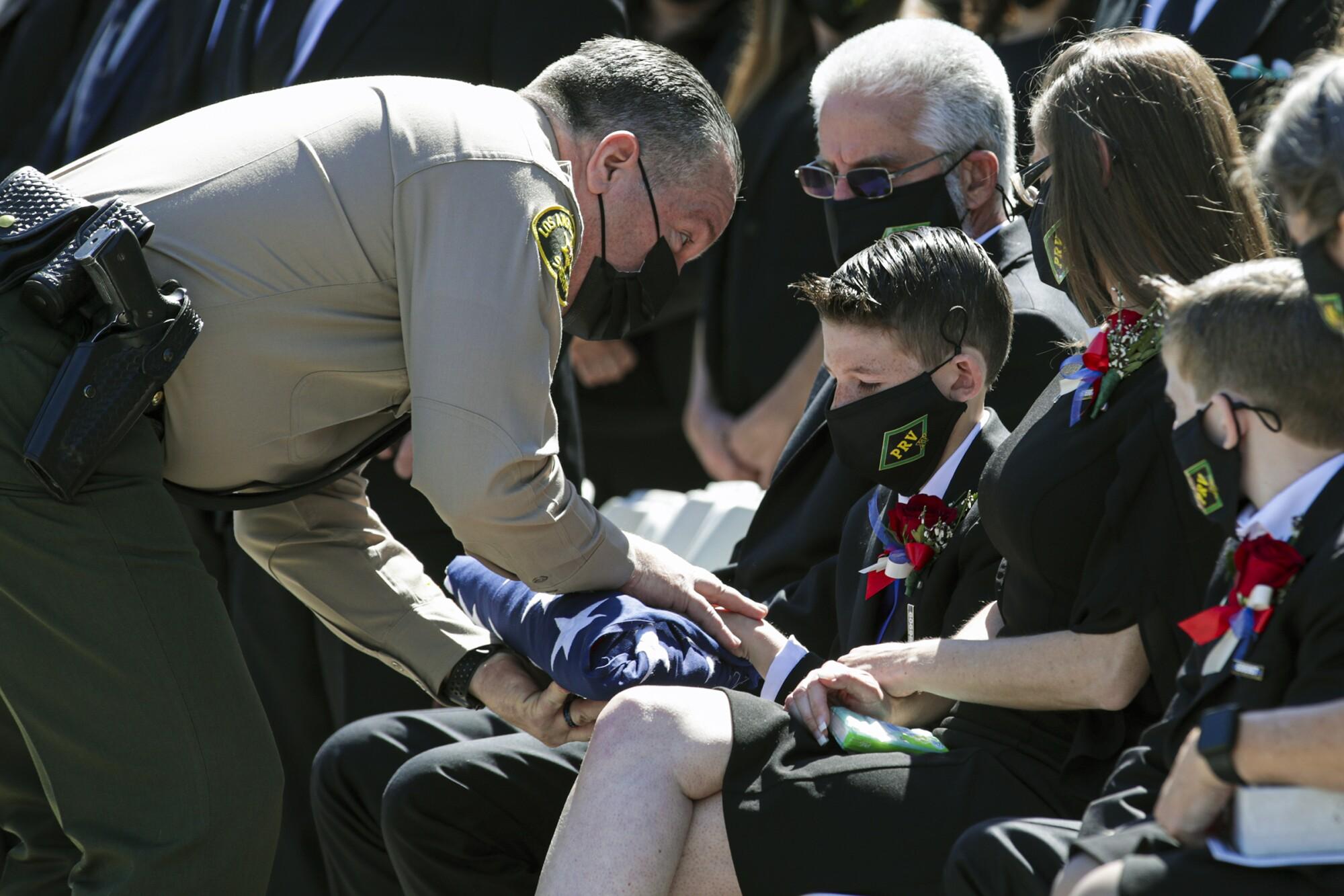 Los Angeles County Sheriff Alex Villanueva presents flag to Landen Albanese, the 11-year-old son of Deputy Thomas Albanese