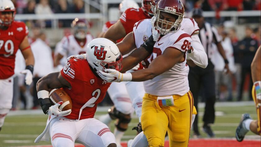 USC defensive lineman Christian Rector tackles Utah running back Zack Moss during the first half on Saturday in Salt Lake City.