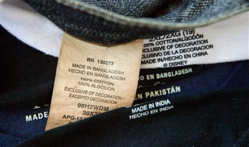 FILE - This Dec. 13, 2012 file photo shows labels of garments made in Bangladesh, India, China and Pakistan, that were purchased at a Wal-Mart store in Atlanta. The rising death toll from the building collapse that killed more than 1,000 garment workers in Bangladesh on April 24, 2013, may force Western brands to make a choice: Stay and work to improve conditions. Or leave and face higher costs, similar or worse worker conditions in other low-wage countries and criticism for abandoning a poor na