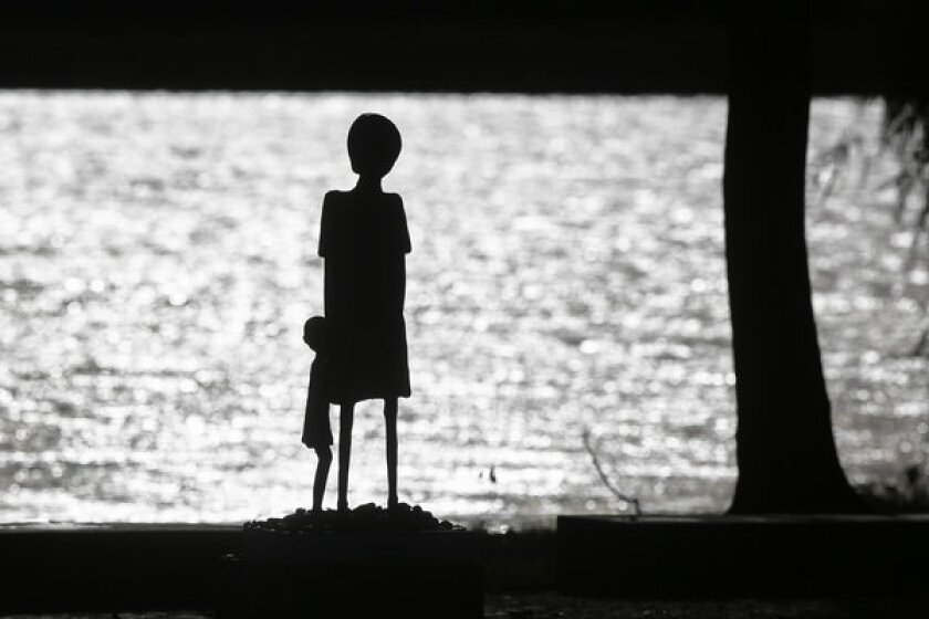 """A sculpture of a woman and a child is silhouetted against the water of Schwedsee lake at Nazi death camp Ravensbrueck. On Nov. 9, Germany remembers the 75th anniversary of the """"Kristallnacht,"""" the night Nazis coordinated a wave of attacks in Germany and Austria, smashing windows, burning synagogues, ransacking homes and looting Jewish-owned stores."""