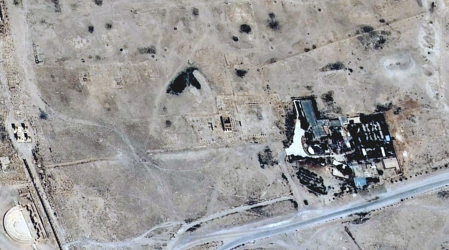 A satellite image of Palmyra, the ancient ruins site in Syria, shows the Temple of Baal Shamin in June before it was destroyed by Islamic militants. The temple is the tiny, vertical rectangle to the left of the cluster of modern buildings. Palmyra's Roman amphitheater can be seen at the bottom left portion of the picture.
