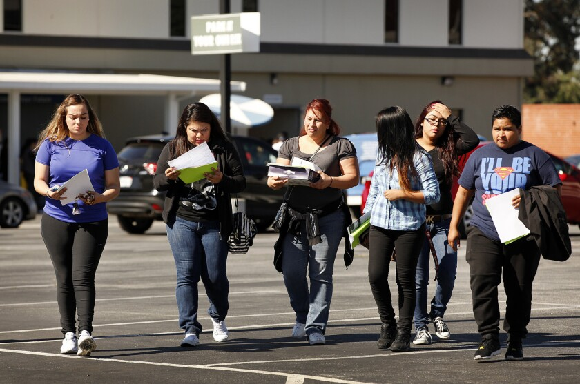 Students at Everest College in Alhambra leave the campus with paperwork on loan forgiveness in April, after Corinthian Colleges abruptly shut down its remaining campuses. The U.S. Department of Education announced an expanded student debt relief plan in June.