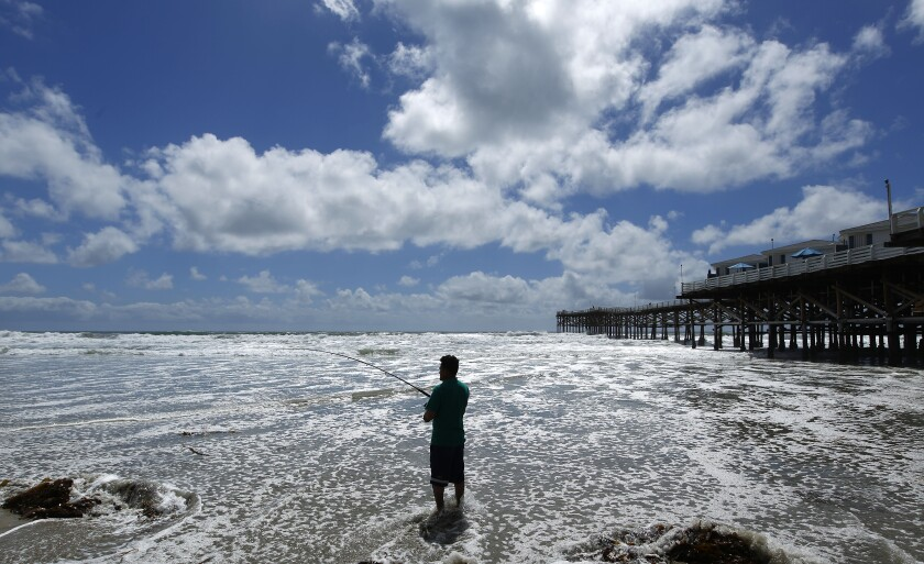 Tony Malagon of San Francisco fishes on a stormy day in Pacific Beach on May 20, 2019. High waves and high winds along with rain are in store for San Diego this week.