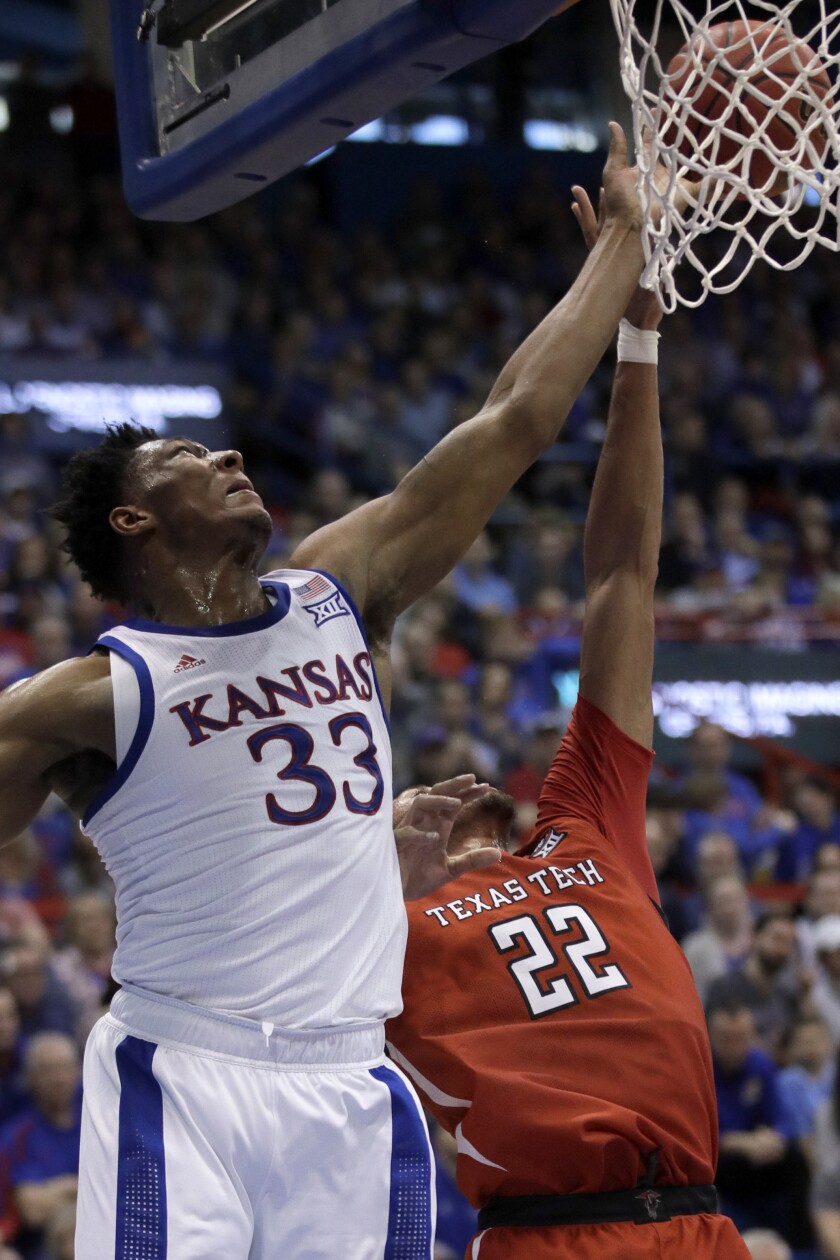 Kansas forward David McCormack (33) shoots while covered by Texas Tech forward TJ Holyfield (22) during the first half of an NCAA college basketball game in Lawrence, Kan., Saturday, Feb. 1, 2020. (AP Photo/Orlin Wagner)