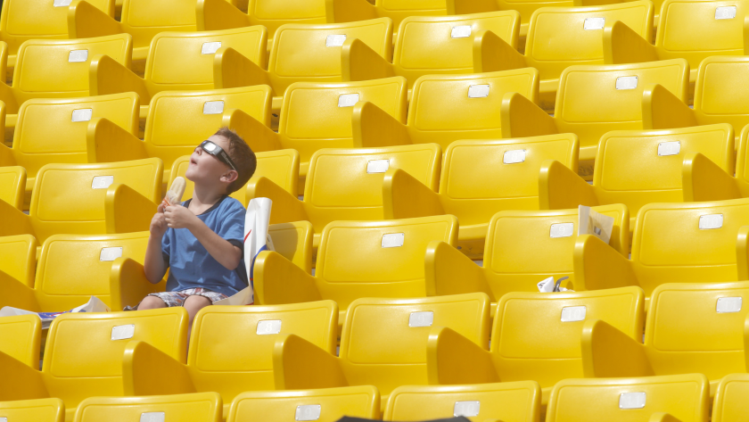 A person sits alone in a field of yellow seats.