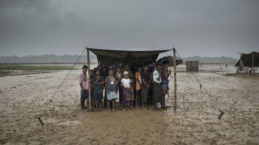 Rohingya Muslim refugees take shelter from the rain during a food distribution at Nayapara refugee camp in Bangladesh in October 2017.