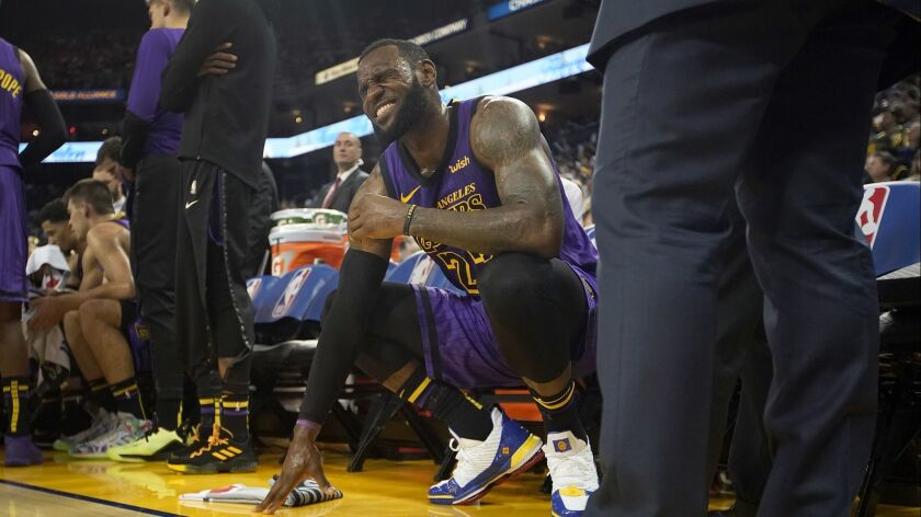 Los Angeles Lakers forward LeBron James (23) grimaces after straining his left groin, during the sec