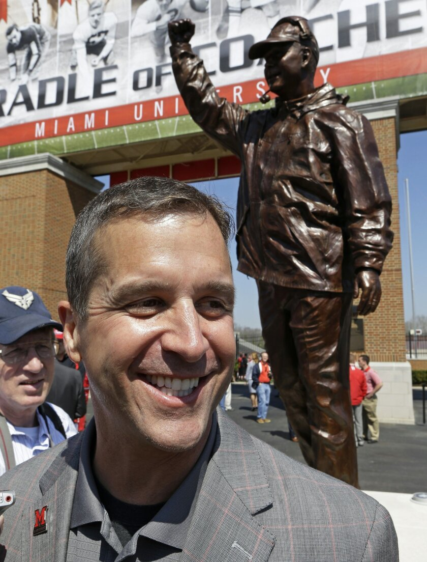 Baltimore Ravens coach John Harbaugh smiles next to a statue of him that was unveiled, Saturday, April 19, 2014, at Miami (Ohio) University in Oxford, Ohio, where Harbaugh was inducted into the school's Cradle of Coaches. (AP Photo/Al Behrman)