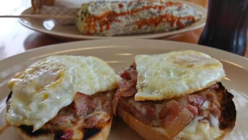 The toasted bolillo halves, topped with bacon, melted cheese over medium fried eggs and all on fresh baked bread are served at Panchita's in North Park. (Amy T. Granite)
