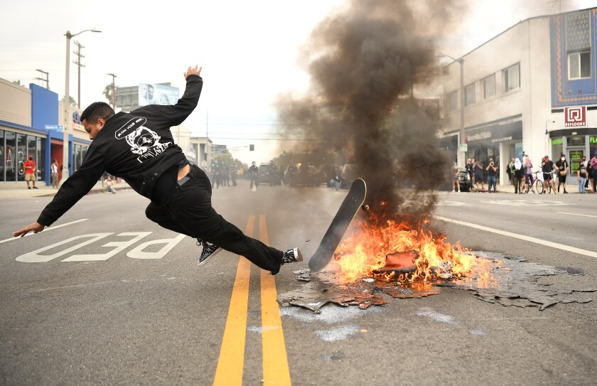 A skateboarder falls over a fire set in the street by protesters in Los Angeles on Saturday.