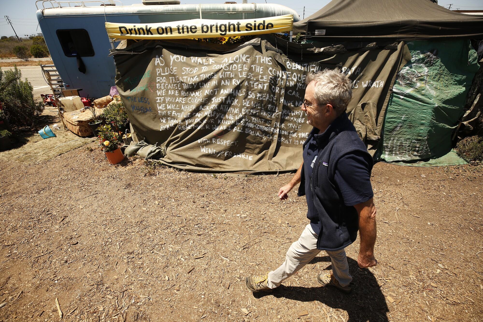 Scott Culbertson, executive director of the Friends of Ballona Wetlands, walks past campers near the Ballona Wetlands.