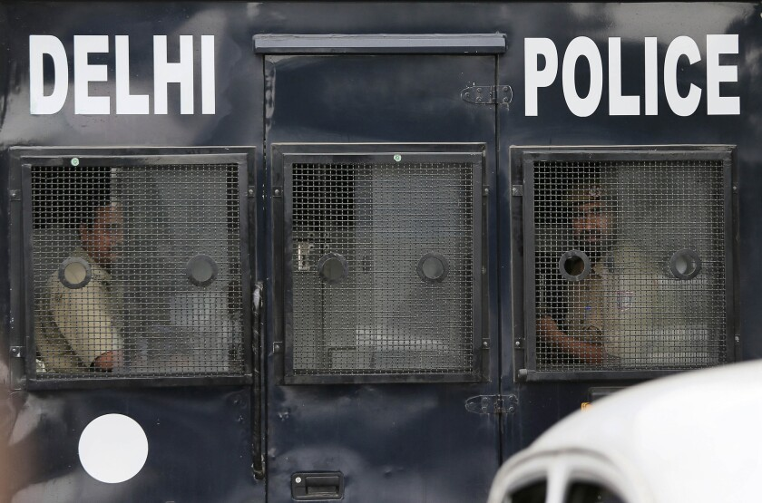 Indian policemen look out from a van carrying four men convicted in the fatal gang rape of a young woman on a New Delhi bus in December.