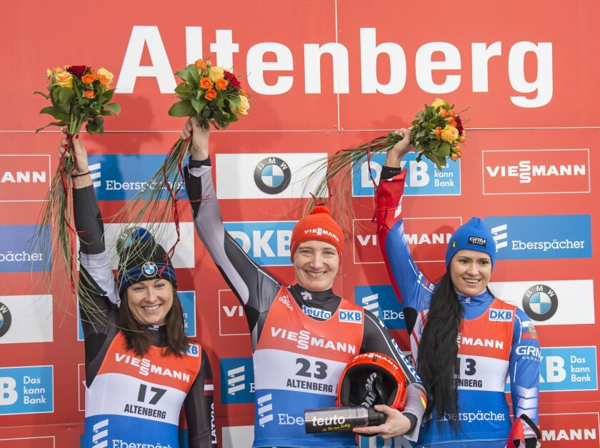 Winner Tatjana Huefner of Germany, center, celebrates besides the second placed Eliza Cauce of Latvia, left, and the third placed Tatiana Ivanova of Russia, right, during the flower ceremony  after  the women's  luge World Cup race in Altenberg, eastern Germany, Sunday, Feb. 14, 2016. (AP Photo/Jen