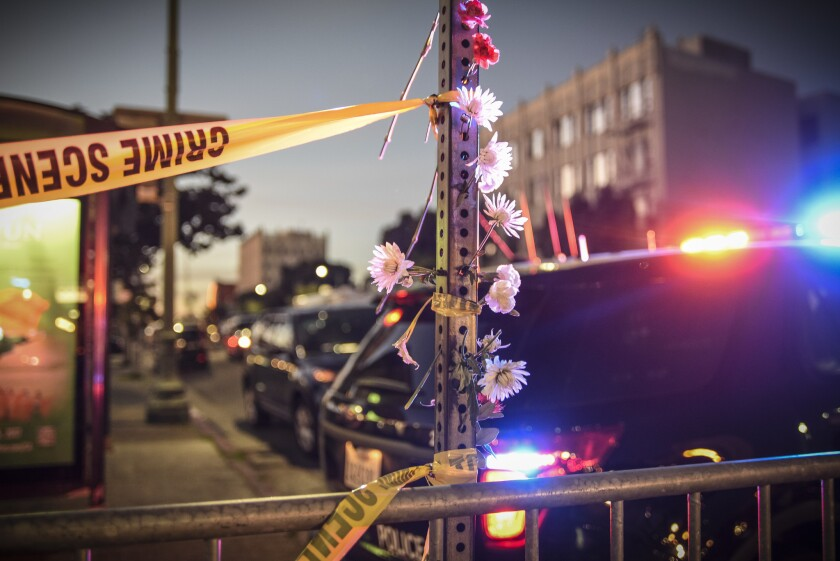 Flowers are left near an Oakland warehouse where a fire broke out during a concert, killing 36 people.