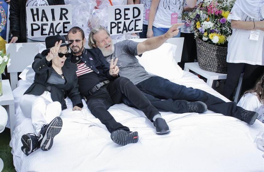 """La artista japonesa Yoko Ono (i), viuda de John Lennon; el ex-Beatle Ringo Starr (c) y el actor Jeff Bridges recrean una """"cama de la paz"""" como la que protagonizó Ono con el cantante en 1969 contra la guerra de Vietnam, hoy, jueves 13 de septiembre de 2018, en Nueva York (EE.UU.). EFE"""