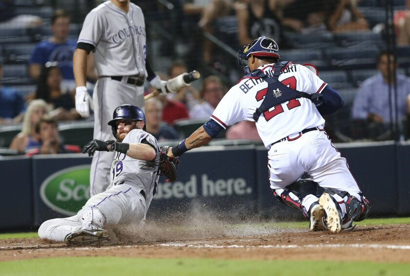 Colorado Rockies' Charlie Blackmon, left, is tagged out at the plate by Atlanta Braves catcher Christian Bethancourt, right, as he tried to score on a Brandon Barnes base hit in the eighth inning of a baseball game Monday, Aug. 24, 2015, in Atlanta. (AP Photo/John Bazemore)