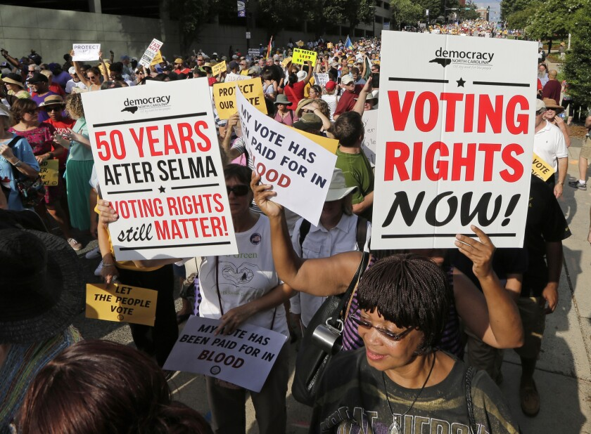 Demonstrators march through the streets of Winston-Salem, N.C. on July 13, 2015, after the beginning of a federal voting rights trial challenging a 2013 state law.