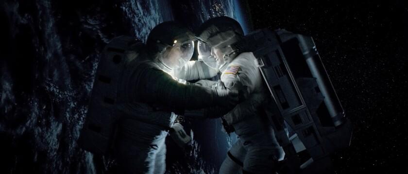 "Sandra Bullock as Ryan Stone and George Clooney as Matt Kowalski in Warner Bros. Pictures' thriller ""Gravity."""