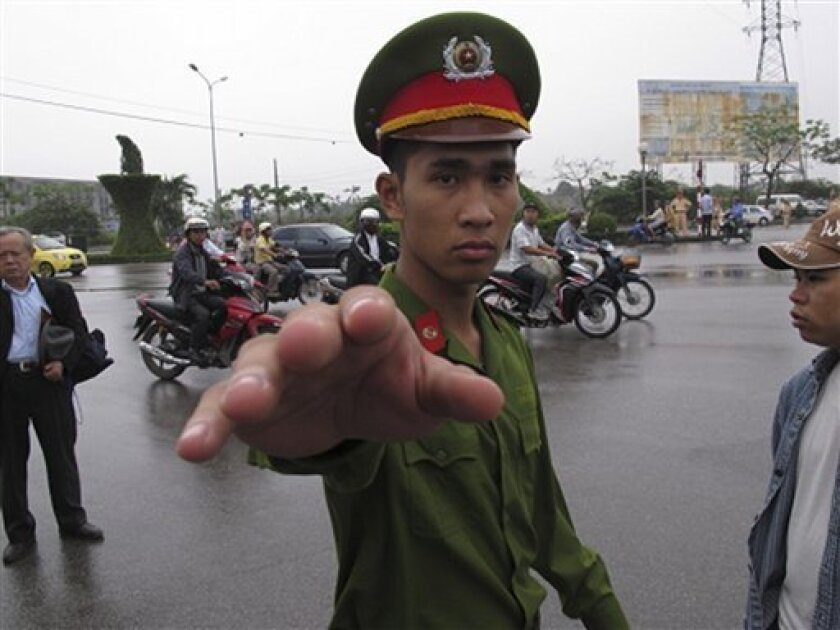 A Vietnamese police officer gestures toward a photographer, seeking to stop him from working close to a court in Haiphong Vietnam, Tuesday, April 2, 2013. A Vietnamese court begun hearing the trial of four fish farmers charged with attempted murder for fighting back against police and army officers