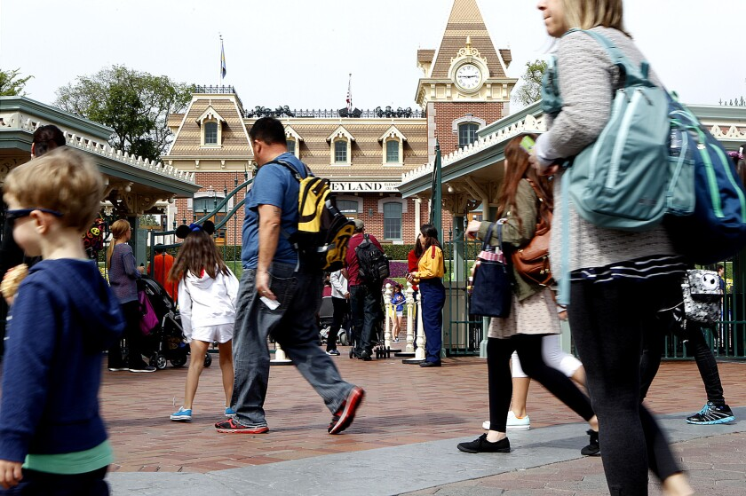 Visitors pass by the entrance gate to Disneyland. The Walt Disney Co. has purchased property near the amusement park, sparking speculation about an expansion.