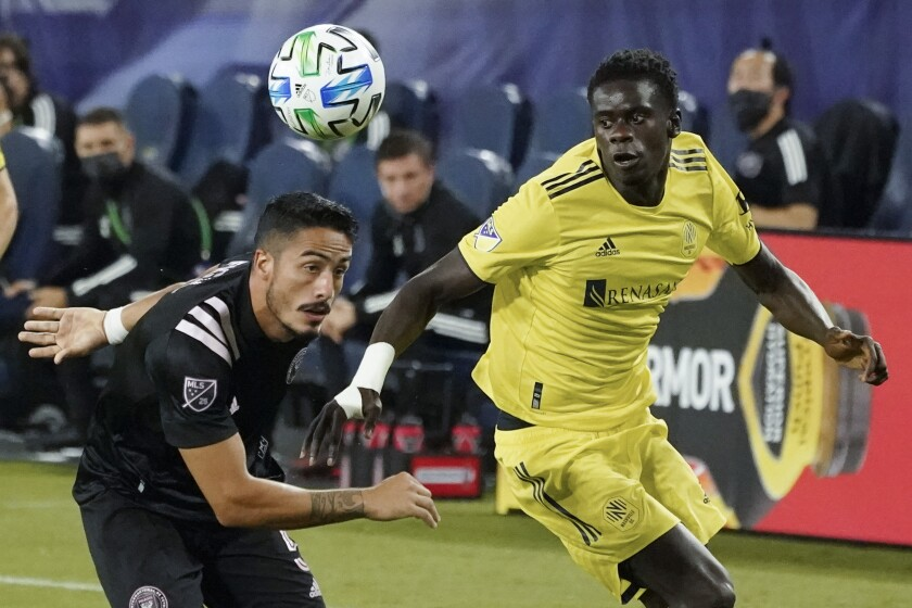 Nashville SC attacker Dominique Badji, right, and Inter Miami defender Nicolas Figal chase after the ball.