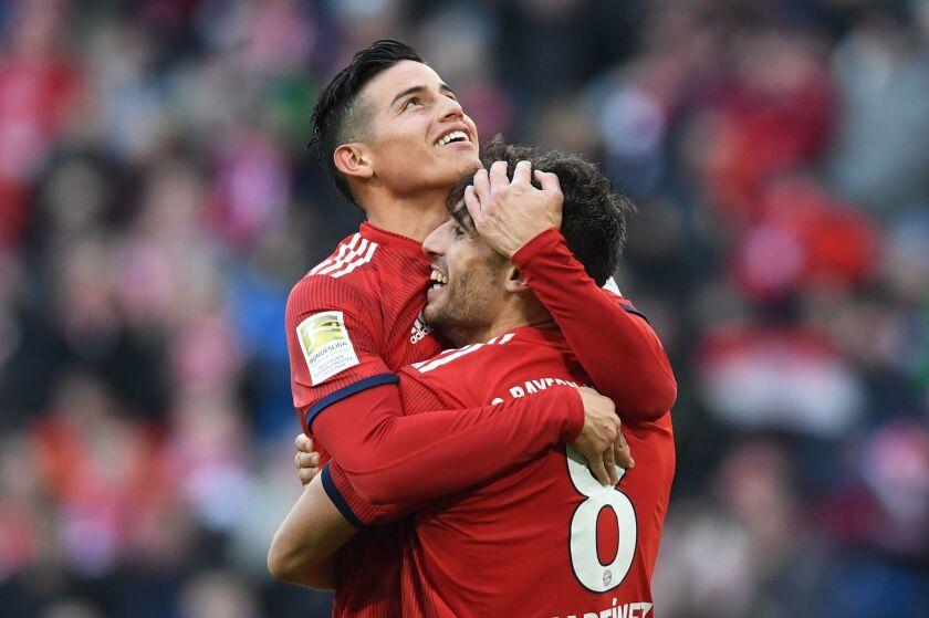 Bayern Munich's Colombian James Rodriguez (L) congratulates Spanish midfielder Javi Martinez after he scored during the German first division Bundesliga football match Bayern Munich vs Hertha Berlin in Munich on February 23, 2019.