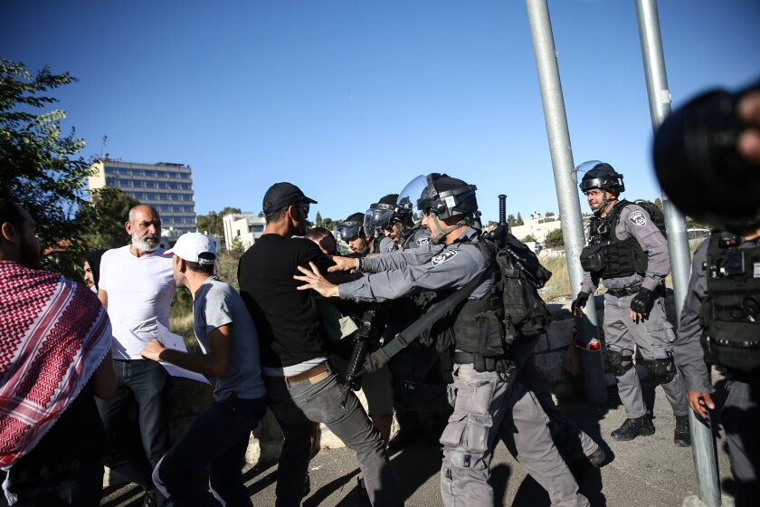 A uniformed man in protective gear pushes a civilian man.